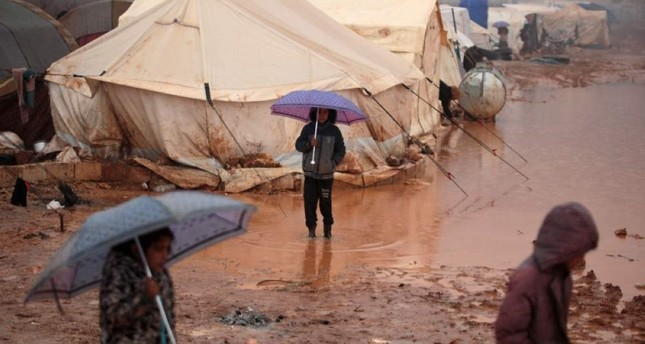Syrian children who fled battles in the southern countryside of the Idlib province walk in mud and water caused by heavy rainfall, in a camp for displaced people in Kafr Dariyan situated at a short distance from Syria's border with Turkey, on Dec. 28, 2019 AFP Photo
