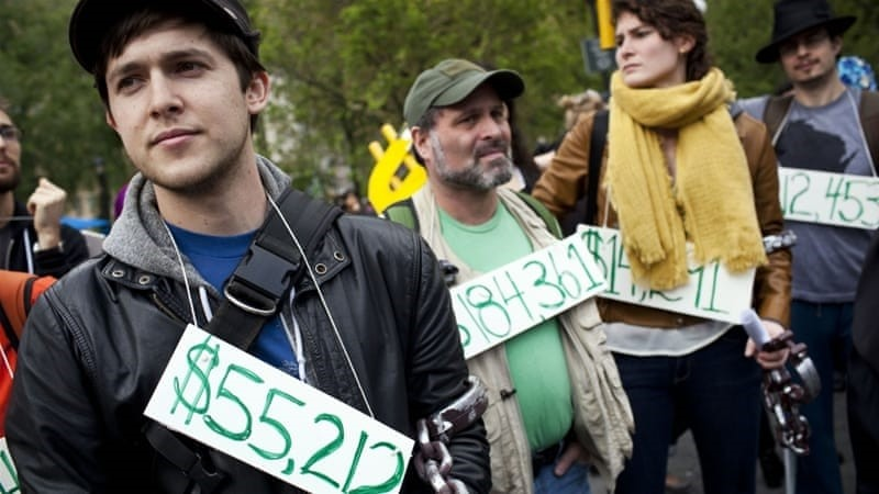 People wear signs around their necks representing their student debt during a protest in New York, April 2012. (Reuters Photo)