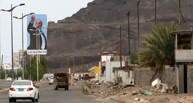 Cars drive beneath a large billboard showing Yemen's internationally recognized government of President Abed Rabbo Manour Hadi, Aden, Aug. 17, 2019.