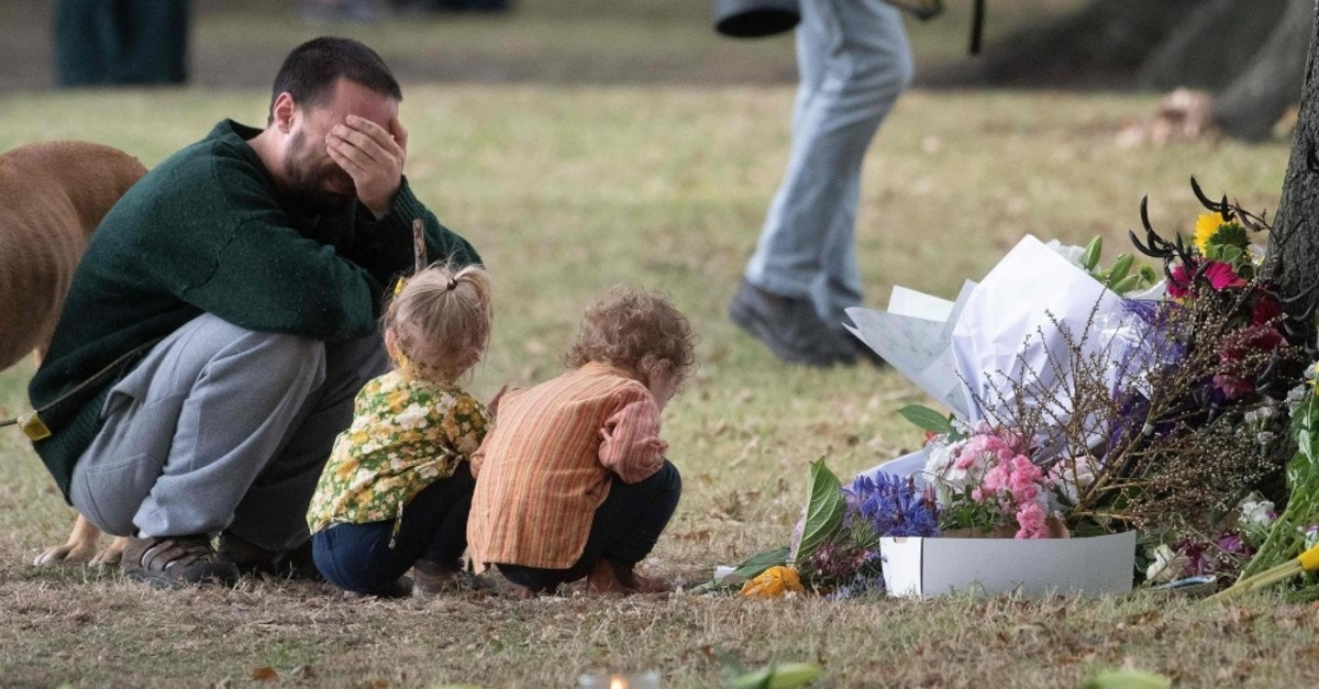A man cries near his children in front of floral tributes for the victims of the twin mosque terror attacks across the road at the Masjid Al Noor mosque in Christchurch, New Zealand, March 19, 2019.