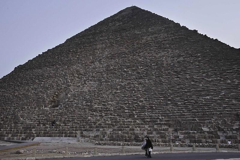 An Egyptian woman walk past the Khufu pyramid in Giza, Egypt, Monday, Nov. 9, 2015. (AP Photo)