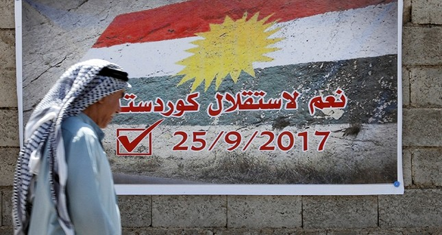A man passes by an independence referendum agitation banner in Kirkuk, Iraq, Sept. 10, 2017. (Reuters Photo)