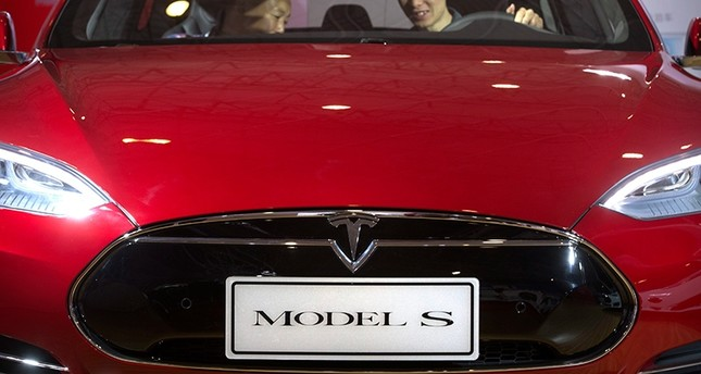In this Monday, April 25, 2016, file photo, a man sits behind the steering wheel of a Tesla Model S electric car on display at the Beijing International Automotive Exhibition in Beijing (AP Photo)