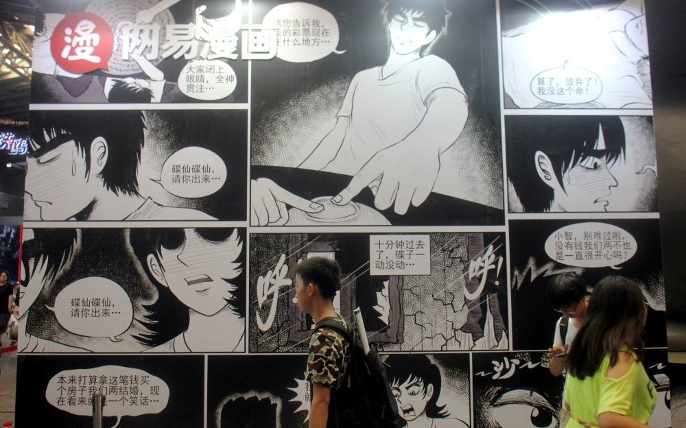 People walk past a booth of NetEase Comics at the China International Cartoon and Game Expo in Shanghai.