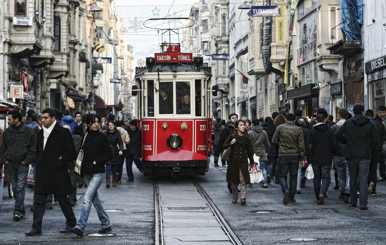 A tramway passes by as people walk on the crowded u0130stiklal street in Istanbul.