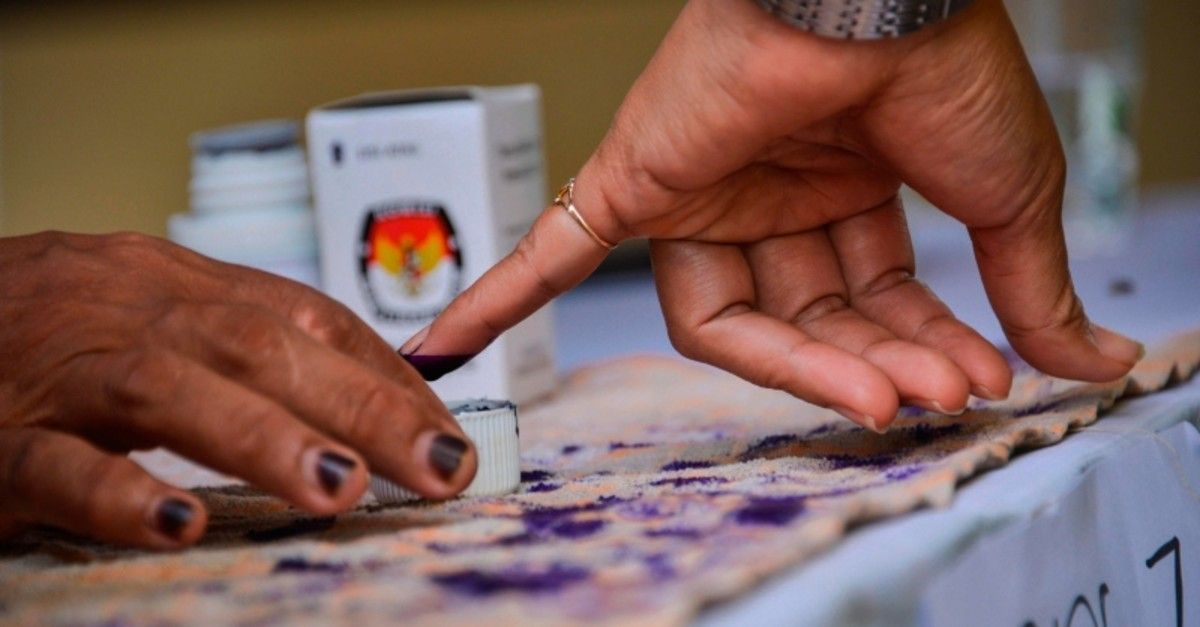 A woman has her finger inked after casting her ballot during a revote due to logistical issues in the country's general election in Banda Aceh on April 25, 2019. (AFP Photo)