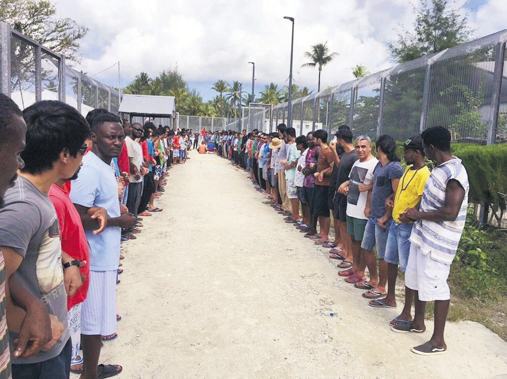 Refugees links hands in solidarity ahead of the center's closure at the Manus Island detention center, Papua New Guinea, Oct. 31.