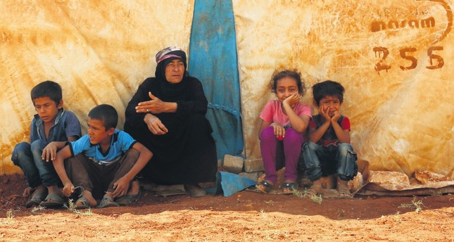 Displaced Syrians sit by a tent at a camp in Kafr Lusin, in Syria's Idlib, near the border with Turkey, Sept. 9.
