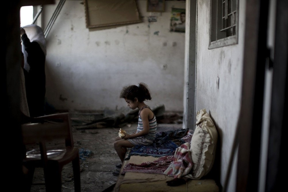 A Palestinian girl sits and eats in the rubble of her destroyed home, Gaza City.