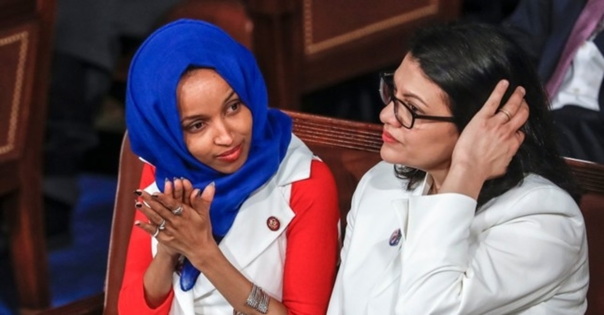 In this Feb. 5, 2019 file photo, Rep. Ilhan Omar, D-Minn., left, joined at right by Rep. Rashida Tlaib, D-Mich., listen to President Donald Trump's State of the Union speech, at the Capitol in Washington (AP Photo)