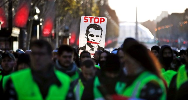 Yellow vests protesters hold a sign saying Stop Macron as they walk down the Champs Elysees avenue to Place de la Concorde during a demonstration in Paris, Dec. 8.