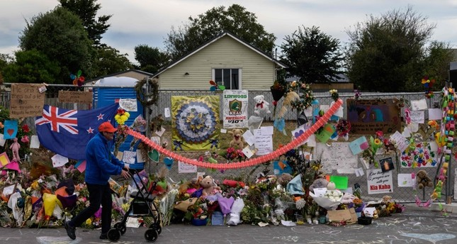 A man walks past flowers and tributes displayed in memory of the twin mosque massacre victims along the road outside the Linwood mosque back C in Christchurch, March 25, 2019.
