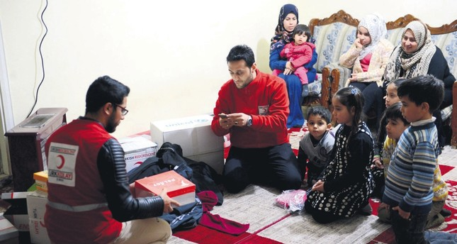 Turkish Red Crescent staff deliver clothes and shoes to al-Ahmad family in the city of Kilis. The family of nine, including quintuplets, relies on aid as the parents are unemployed.