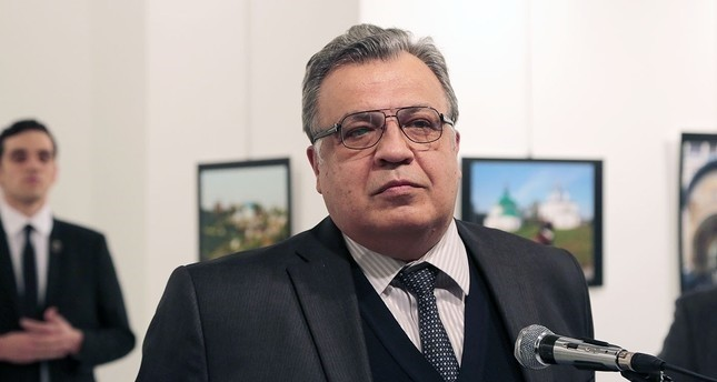 The Russian Ambassador to Turkey Andrei Karlov speaks a gallery in Ankara Monday Dec. 19, 2016. The gunman is seen at rear on the left. (AP Photo)