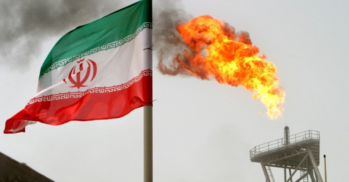 A gas flare on an oil production platform in the Soroush oil fields is seen alongside an Iranian flag in the Persian Gulf, Iran (Reuters File Photo