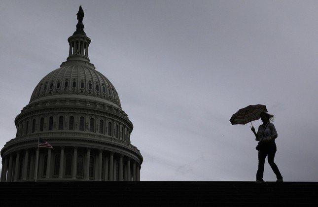 A visitor walks across the east front of the U.S. Capitol during a rain storm in Washington Sept. 30, 2019.(Getty Images via AFP)