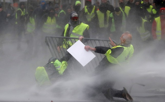 Demonstrators get hit by a water cannon during a protest of the yellow jackets in Brussels, Friday, Nov. 30, 2018. (AP Photo)