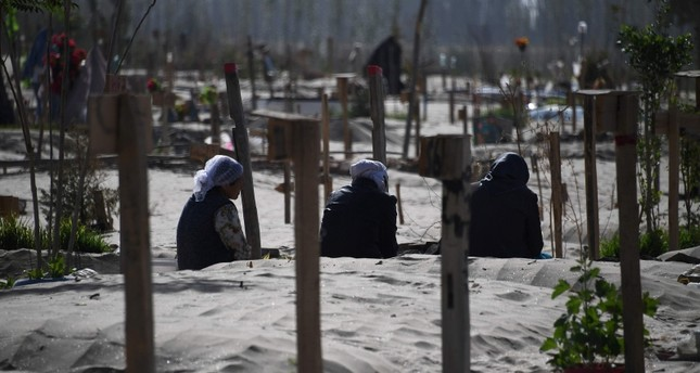 This photo taken on May 31, 2019 shows Uighur women praying in a graveyard on the outskirts of Hotan in China's northwest Xinjiang region AFP Photo