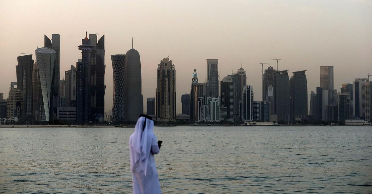 A man looks at his phone on the corniche of the Qatari capital Doha, July 2, 2017.