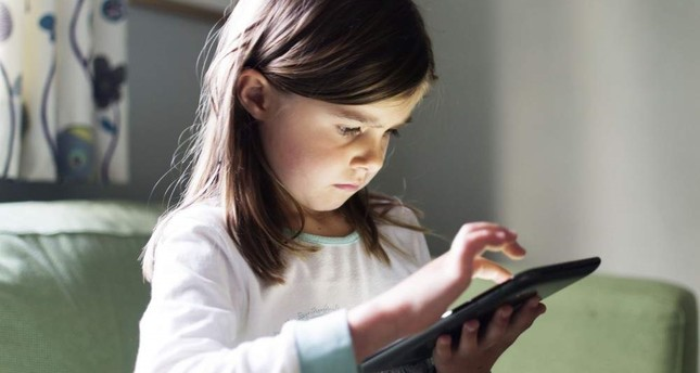 A young girl uses a tablet computer late at night with the glow from the screen on her face. iStock