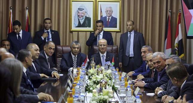Palestinian Prime Minister Rami Hamdallah, center, heads a meeting with officials at Palestinian President Mahmoud Abbas' former official residence, in Gaza City, Tuesday, Oct. 3, 2017. (AP Photo)