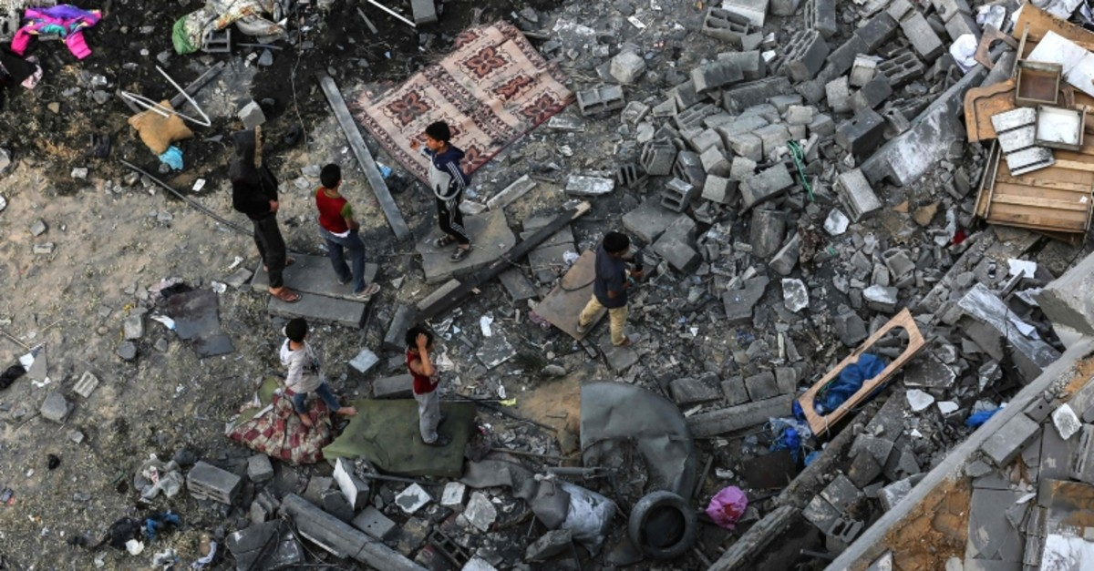 Palestinians children on May 6, 2019, gather among the rubble of a building that was destroyed during Israeli airstrikes on Gaza City. (AFP Photo)