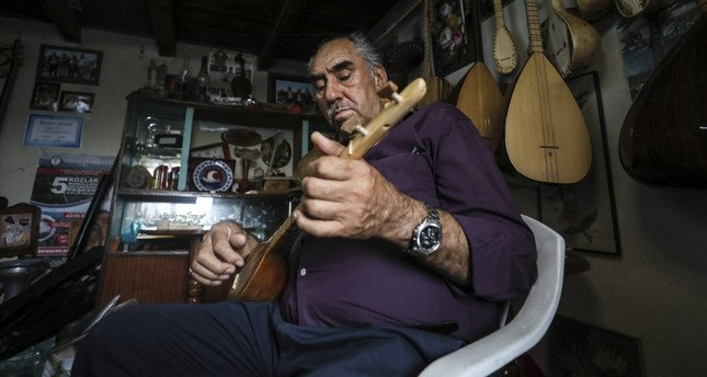 Bayram Dev plays the instrument he produced in his workshop.