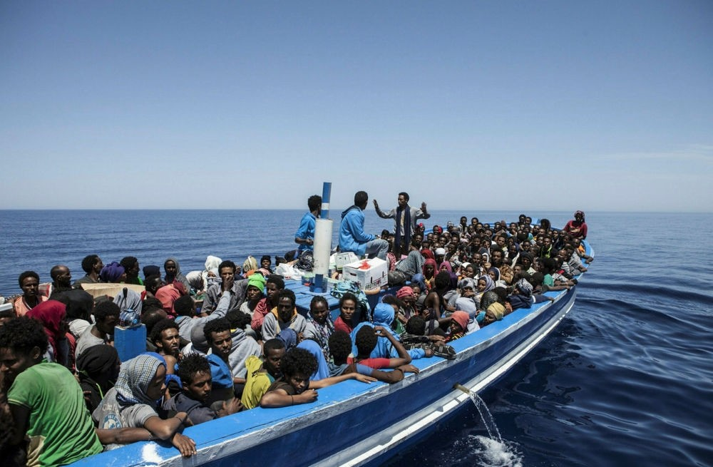 Migrants aboard a wooden boat on the Mediterranean as they try to reach Europe.