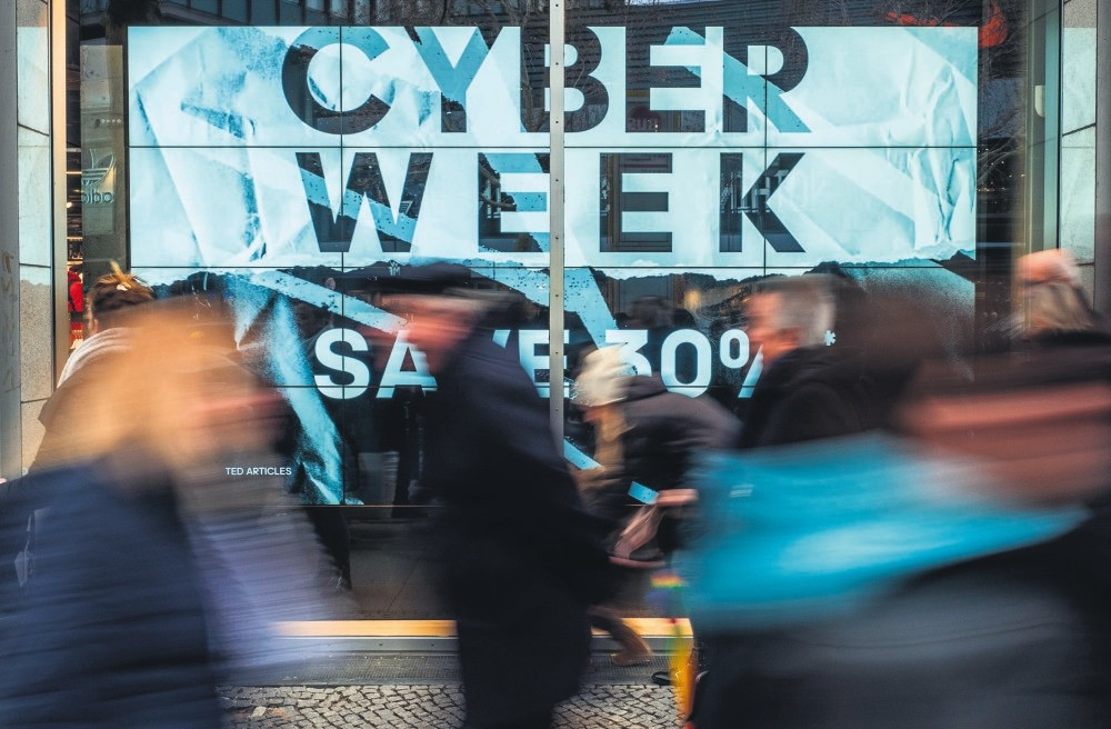 Shoppers walk past a store advertising a so-called ,Cyber Week, sale, in Berlin, Nov.23.