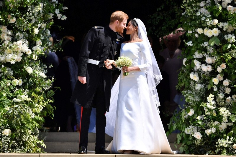 Britain's Prince Harry, Duke of Sussex kisses his wife Meghan, Duchess of Sussex as they leave from the West Door of St George's Chapel, Windsor Castle, in Windsor, on May 19, 2018 after their wedding ceremony. (AFP Photo)