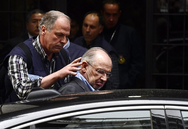A file picture taken on April 16, 2015 shows a member of the police (L) assisting former IMF head and ex economy minister with Spain's ruling conservative party Rodrigo Rato (C) into a vehicle outside his home in Madrid. (AFP Photo)