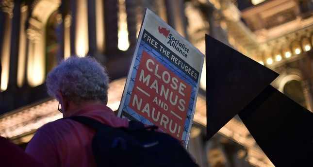 A man with a placard in protest of Australia's immigration policy during a candlelight vigil in Sydney on April 30 for an Iranian refugee who died three days after he set fire to himself on the remote Pacific island of Nauru.