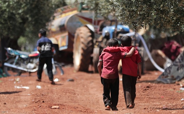 Displaced Syrian children walk together in an olive grove in Idlib province, May 15, 2019.