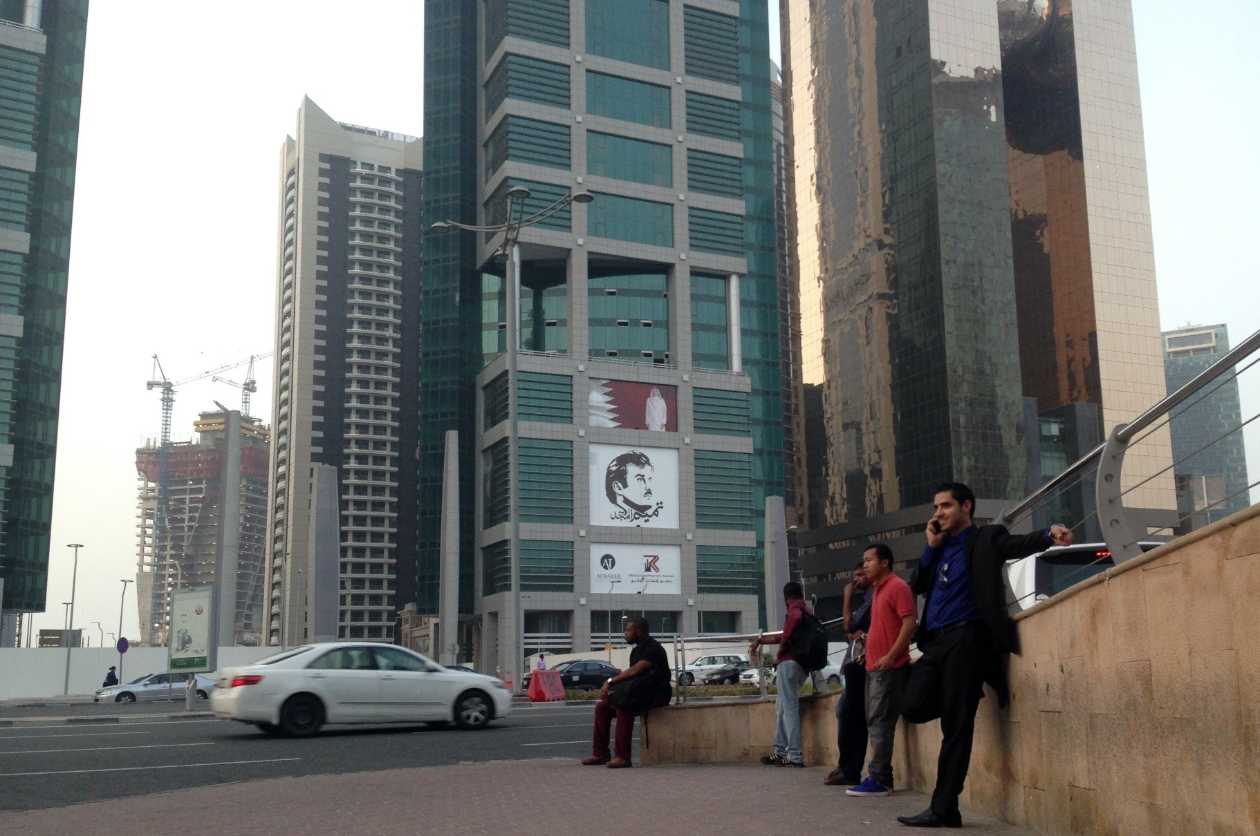 Men wait for a bus in front of a building with the poster of Qatari Emir Sheikh Tamim bin Hamad Al Thani, on July 9, 2017 photo.