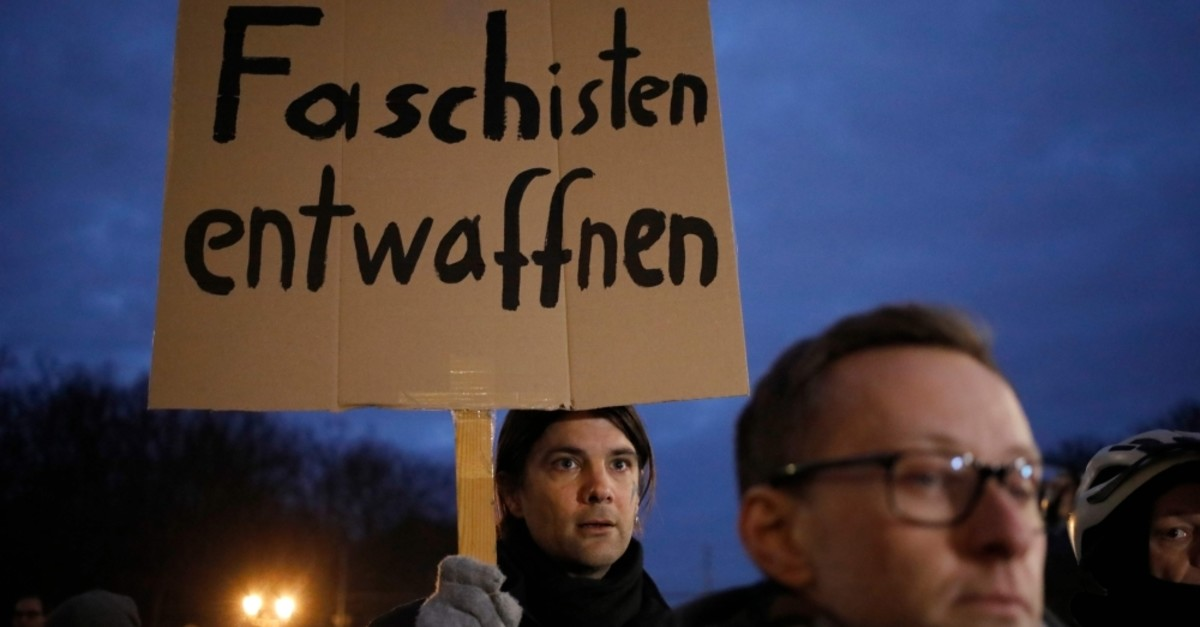 A man holds a poster reading ,Disarm fascists, during a vigil in solidarity with the victims and their families of the Hanau killings in front of the Brandenburg Gate in Berlin, Feb. 20, 2020. (AFP Photo)