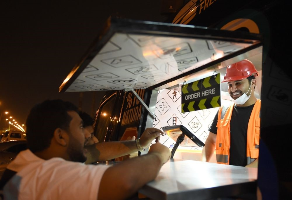 Bader al-Ajmi, 38,(R) owner of ,One Way Burger, serves customers from his truck at a main street in the capital Riyadh.