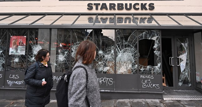 Graffiti is seen on a vandalized Starbucks coffee shop with broken store front windows the day after clashes during a national day of protest by the yellow vests movement in Paris, France, December 9, 2018. (AA Photo)