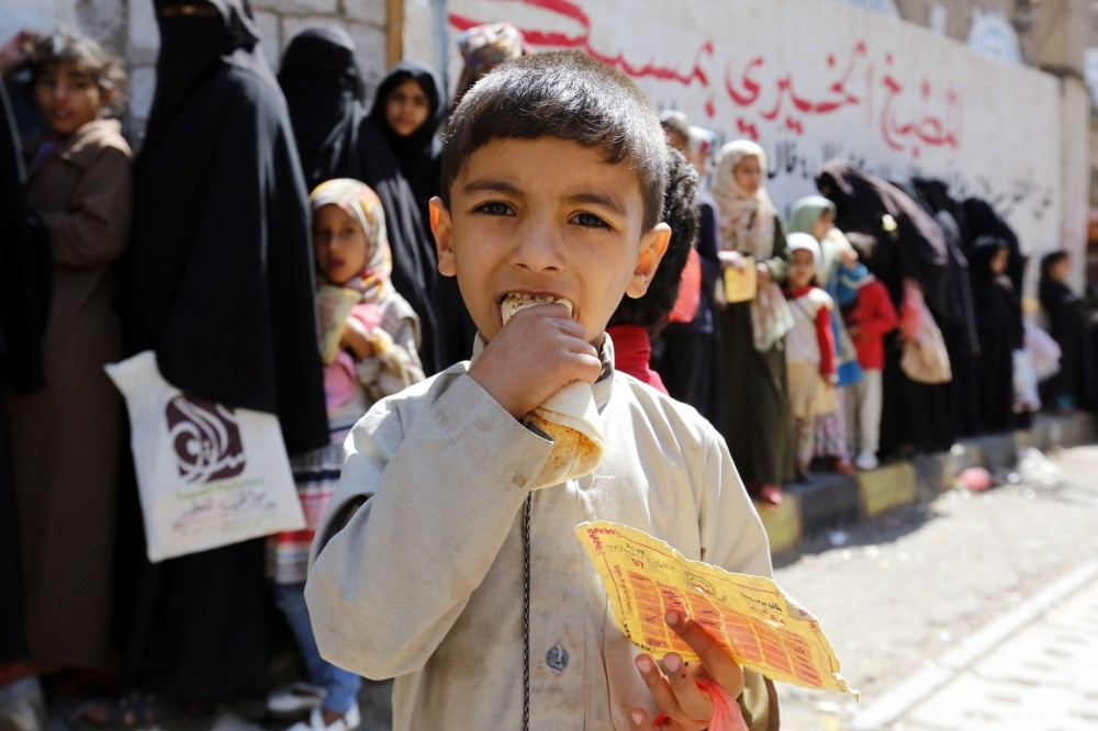 A conflict-affected child eats a loaf of bread after receiving food from a local charity, Sanaa, Nov. 3.