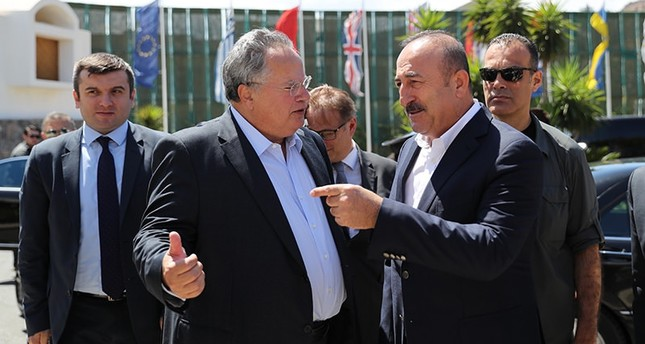 Turkish FM Mevlüt Çavuşoğlu (R) was greeted by his Greek counterpart Nikos Kocias at the entrance of the hotel in the town of Elounda. (AA Photo)