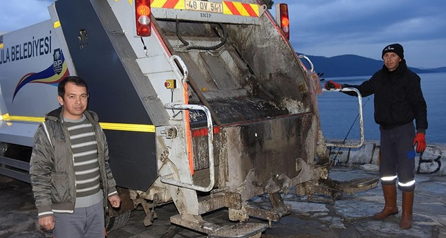 Feridun Özsoy (L), village headman of Muğla's Akyaka neighborhood, works an evening shift as garbage truck driver. (DHA Photo)