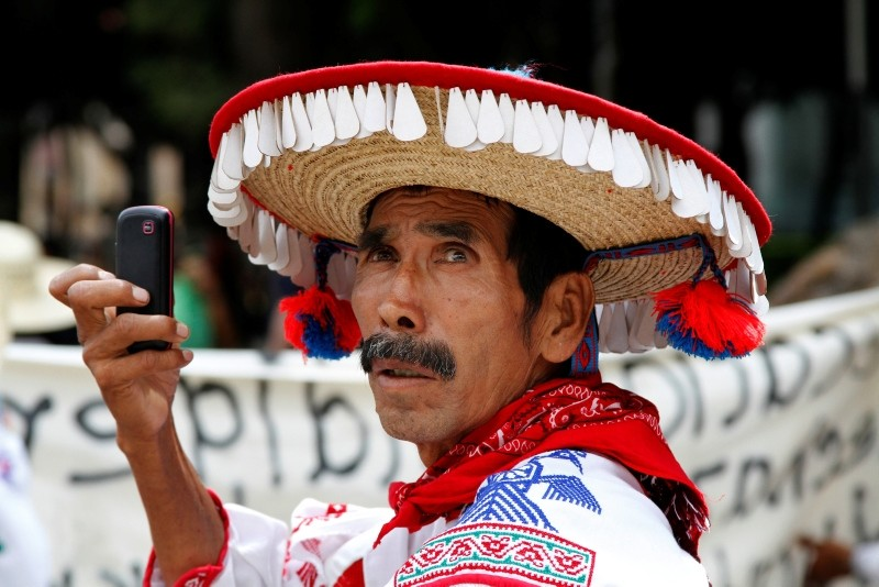 In this Oct. 12, 2013 file photo, a striking teacher from the Guichol Indian community in northern Mexico uses his cell phone during a march by unionized teachers in Mexico City. (AP Photo)
