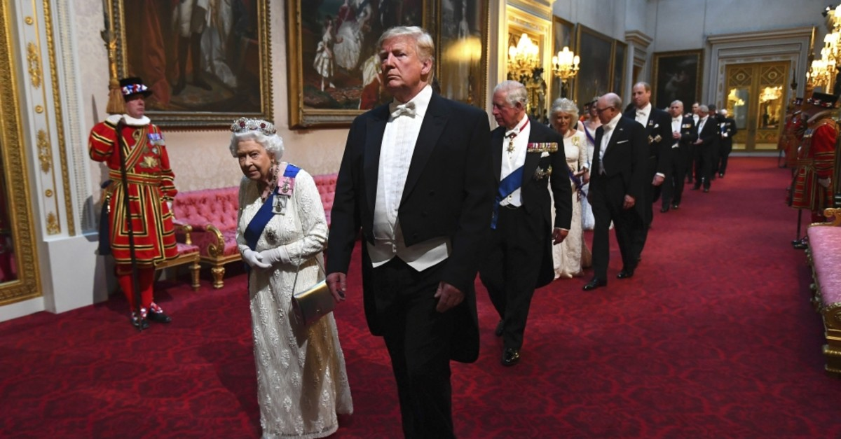 Queen Elizabeth II (L), U.S. President Donald Trump (C) and others arrive through the East Gallery ahead of the State Banquet at Buckingham Palace, London, June 3, 2019.