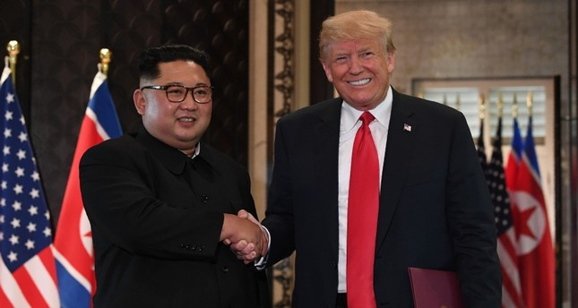 U.S. President Donald Trump and North Korea's leader Kim Jong Un shake hands following a signing ceremony during their historic U.S.-North Korea summit, at the Capella Hotel on Sentosa island in Singapore on June 12, 2018. (AFP Photo)