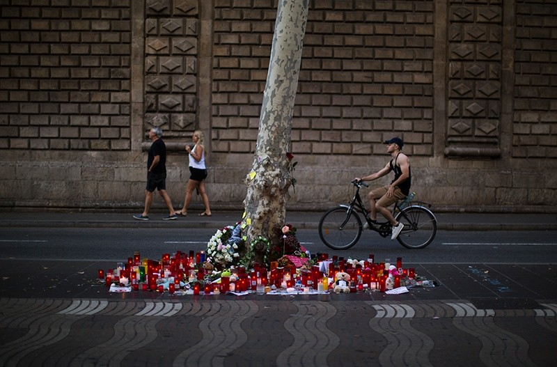 Candles and flowers are placed on the ground after a Daesh-claimed terror attack that killed 14 people and wounded over 120 in Barcelona, Spain, Sunday, Aug. 20, 2017. (AP Photo)