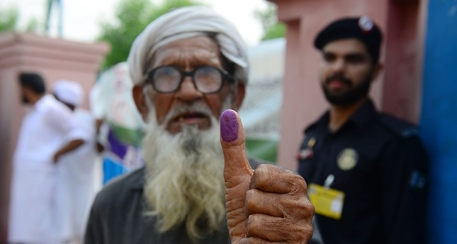An elderly Pakistani man shows his inked thump after casting his vote outside a polling station during general election in Lahore on July 25, 2018. (AFP Photo)