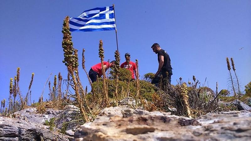 Unidentified individuals hoisting a Greek flag on an islet off Turkey's Didim coast (Sabah Photo)