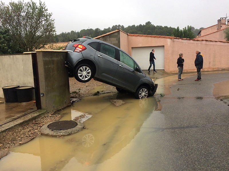 Residents stand by a car swept away by floods on Oct. 15, 2018 in Villegailhenc, near Carcassone, southern France. (AFP Photo)
