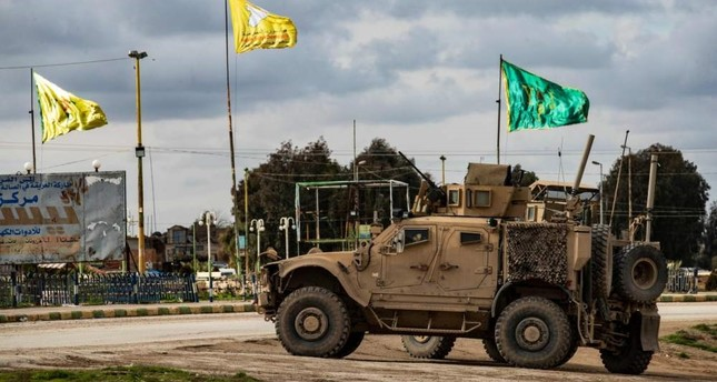 A patrol of US military vehicles is seen near the flying yellow flags of the terrorist YPG-dominated SDF and green flags of its constituent YPJ in the town of Tal Tamr in the northeastern Syrian Hasakah province along the border with Turkey on Feb. 8, 2020. AFP Photo