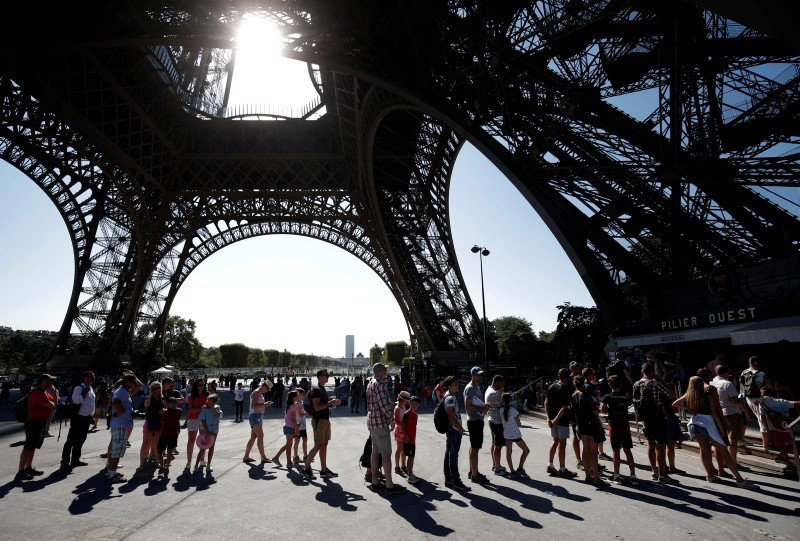 People stand in line at an information booth following the closure of the Eiffel Tower as part of a strike by employees over lengthening queues during the peak summer tourist season in Paris, France, August 2, 2018. (Reuters Photo)