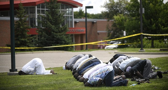 Mohamed Omar, left, the executive director of the Dar Al Farooq Center Islamic Center leads afternoon prayers outside the police tape surrounding the center Saturday Aug. 5, 2017 AP Photo